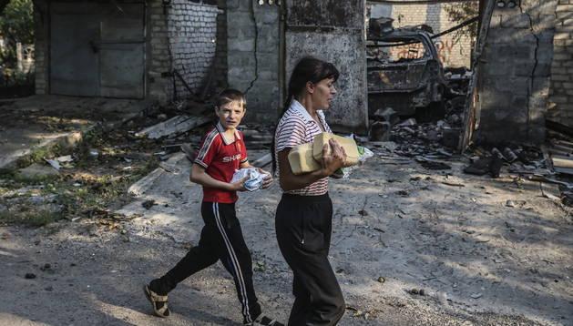 Unos refugiados se abastecen de comida en Ilovaysk, este de Ucrania.