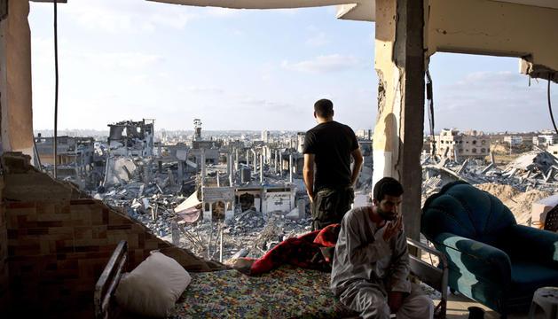 Dos hombres, en su vivienda bombardeada al norte de Gaza