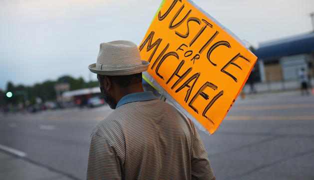 Un manifestante camina por las calle de Ferguson tras pedir justicia para Brown.