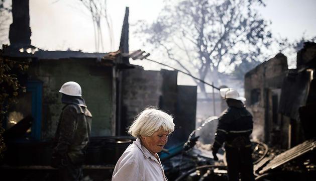 Una mujer, junto a los restos de su casa incendiada en Donetsk