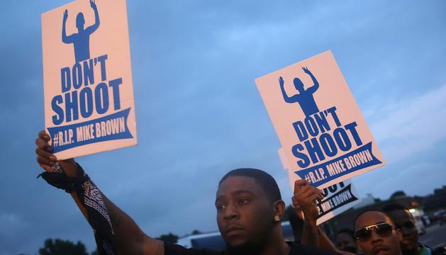 Varios hombre se manifiestan en contra de la muerte de Brown en un tiroteo policial