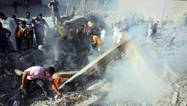 Varios palestinos entre los escombros de un edificio