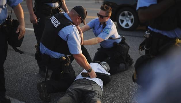 Un joven es arrestado en Fergson, centro de los disturbios raciales de estos días en EE UU.
