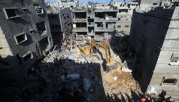 Una excavadora retira escombros en una casa derruida en Rafah