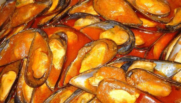 Un plato de mejillones con salsa picante