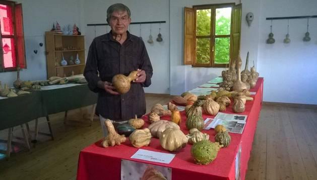 El artista Miguel Marzo, junto a las calabazas de su exposición, en la sala de la antigua escuela.