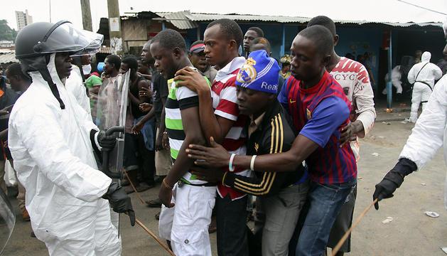 Un policía liberiano controla a varios residentes que viven en West Point, barrio que se encuentra en cuarentena