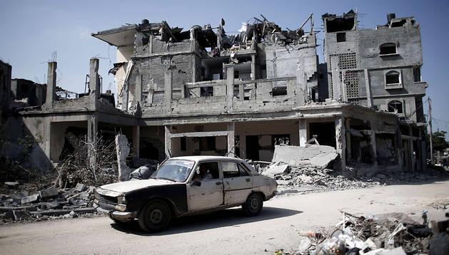 Un conductor palestino delante de un edificio destrozado