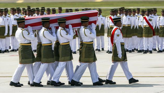 Integrantes del Regimiento Real Malayo cargan un ataúd en la ceremonia de llegada de los cuerpos de las víctimas del accidente del vuelo MH17.