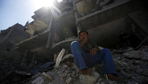 Un niño palestino descansa sobre una pila de escombros