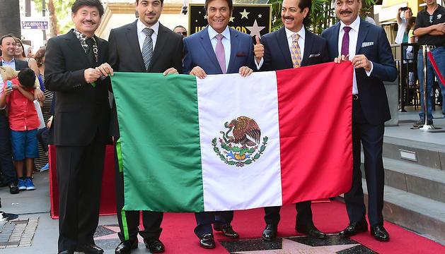 De izquierda a derecha, los integrantes de la banda mexicana Los Tigres del Norte Óscar Lara, Luis Hernández, Hernán Hernández, Jorge Hernández y Eduardo Hernández posan con la bandera mexicana