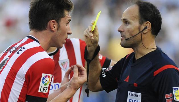 Mateu Lahoz muestra una tarjeta amarilla a Laporte durante el encuentro