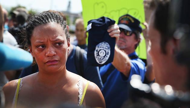 La portavoz de la familia de Michael Brown, Sondra Fifer, habla con un oficial de policía