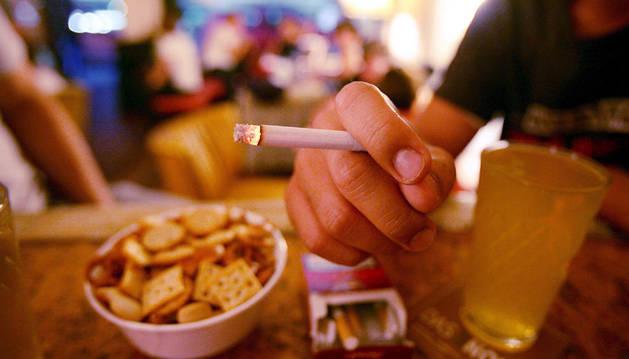 Una persona se fuma un cigarrillo mientras toma una caña y un aperitivo en un local