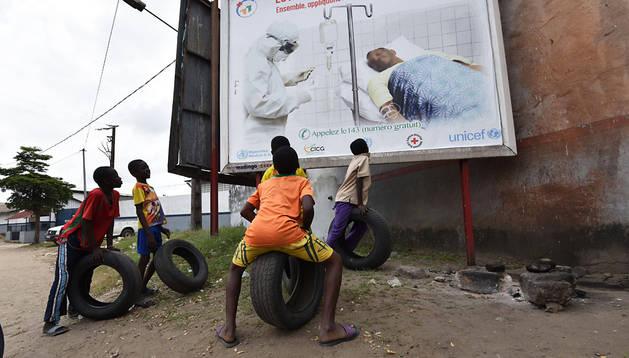 Un grupo de niños mira un cartel de alerta sobre el ébola en la localidad marfileña de Abidjan