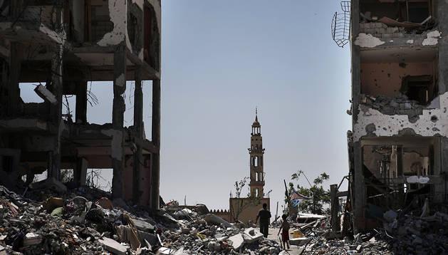 Dos personas caminan entre los escombros de edificios en la localidad de Beit Hanun