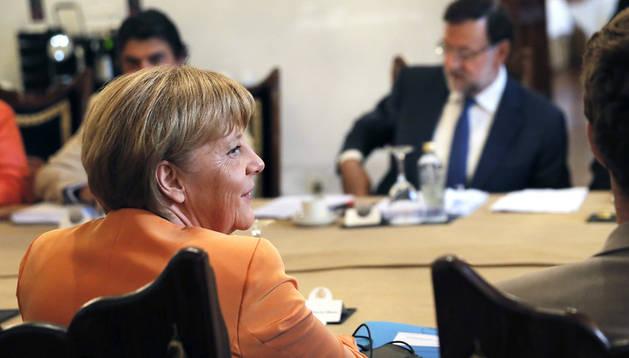 El presidente del Gobierno, Mariano Rajoy (fondo) y la canciller alemana, Angela Merkel,iz., durante la reunión de trabajo en Santiago de Compostela