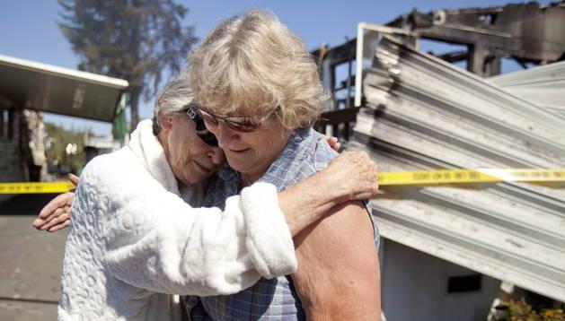 Dos personas desconsoladas junto a los restos de su casa.