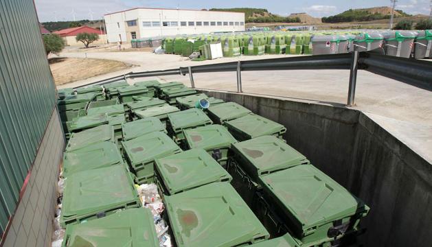 En primer plano, parte de los contenedores antiguos que van a ser subastados -al fondo, los nuevos instalados en Tudela.