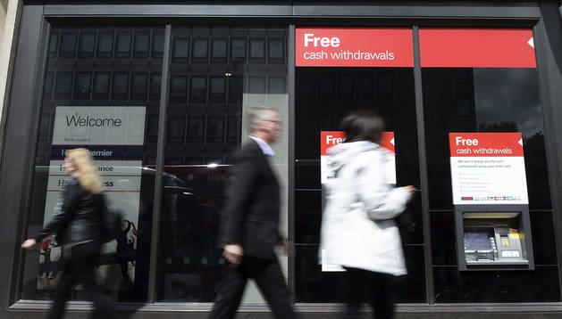 Varias personas pasan frente a una sucursal bancaria