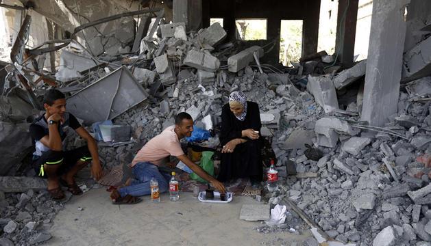 Una familia palestina toma café este miércoles entre las ruinas de su casa