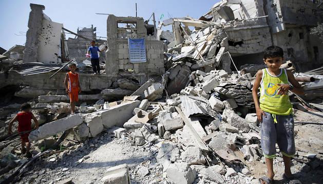 Niños palestinos investigan entre las ruinas de edificios destruídos en el barrio de Al Sejaiya, al este de Gaza