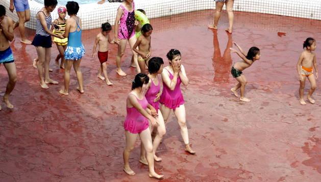 Tres jóvenes norcoreanas caminan después de darse un baño en una de las piscinas del parque acuático de Munsu, en Pyongyang.