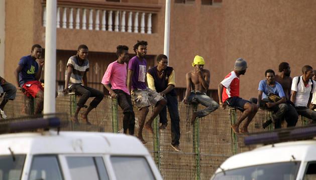 Alrededor de treinta inmigrantes de origen subsahariano permanecen encaramados en la parte alta de la valla de Melilla