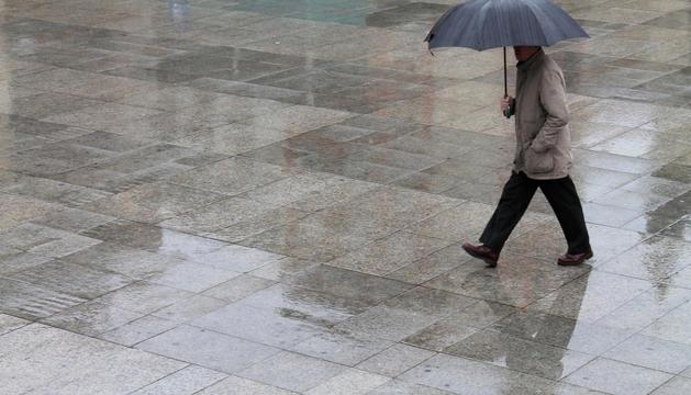 Una persona pasea con paraguas en Pamplona