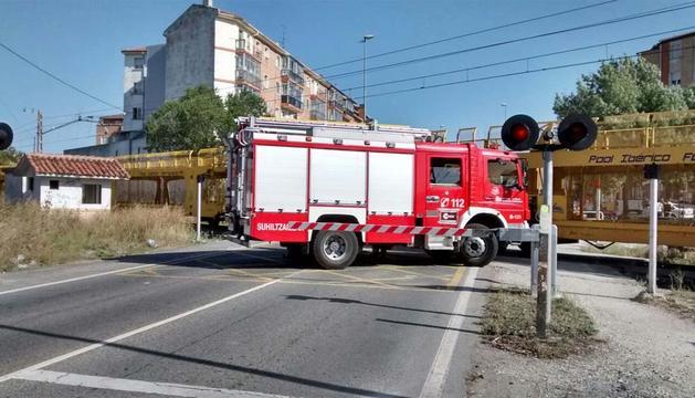 Un camión de bomberos, junto al tren sobre la vía.
