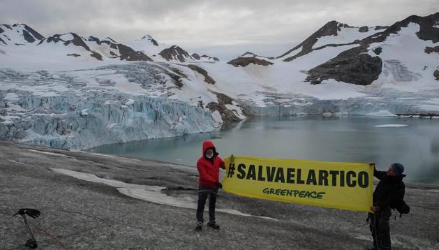 Unos activista de Greenpeace despliegan una pancarta en el Ártico.