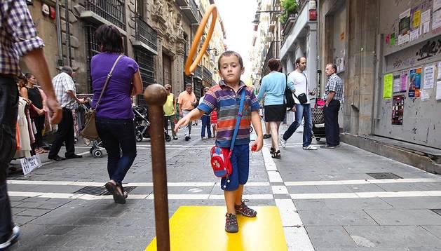 Un niño juega en la calle Mayor con juguetes de madera tradicionales.