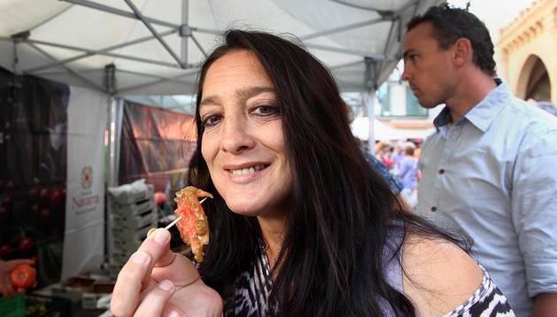 Una persona degusta un trozo de tomate en la 1ª Feria de Tomate Antiguo.
