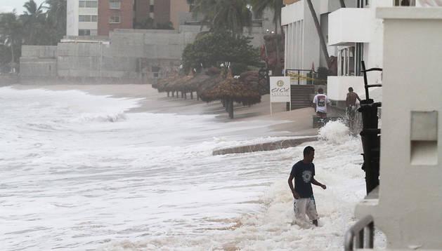 Tres personas tratan de caminar ante la fuerza de las olas en el puerto de Mazatlán