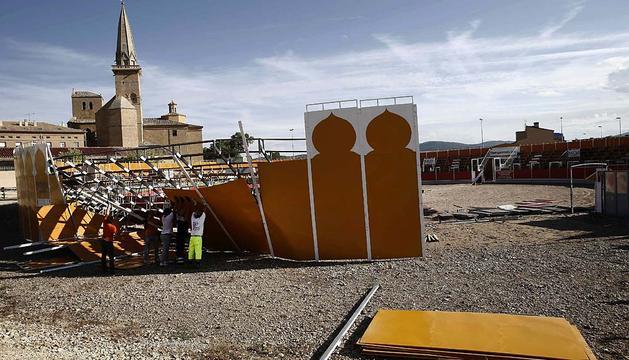 Un grupo de operarios desmonta una de las partes de la plaza de toros de Olite derrumbada.