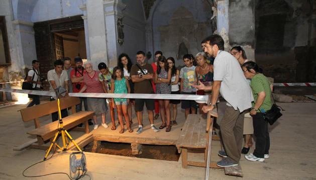 Juanjo Bienes, a la derecha en primer término, explica a los presentes en la visita guiada a las excavaciones de San Nicolás uno de los enterramientos encontrados.