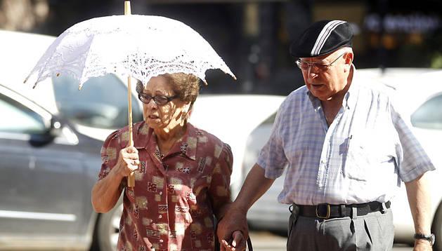 Una mujer, protegiéndose del sol con una sombrilla por el calor