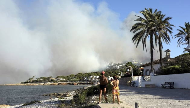 Dos personas observan el humo del incendio forestal declarado esta tarde en el término municipal de Jávea (Alicante)