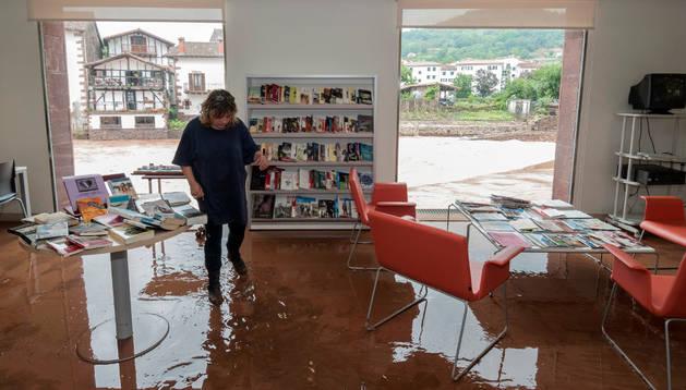 En la imagen de julio, la bibliotecaria Sonia López Igartua contempla los daños de la inundación