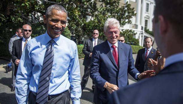 El presidente estadounidense Barack Obama (izda.) conversa con el ex presidente Bill Clinton (dcha.) tras el acto en la Casa Blanca