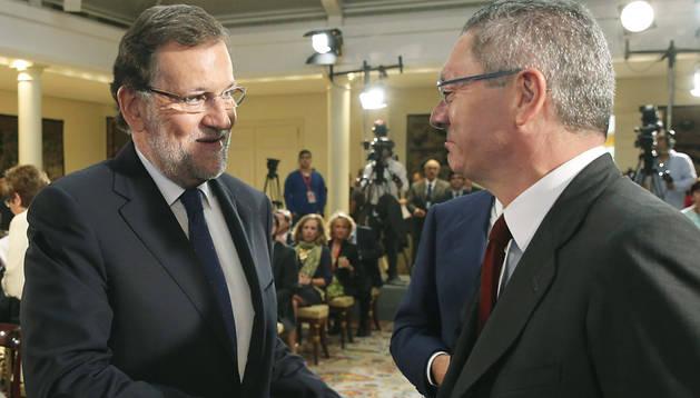 Mariano Rajoy (izda.) estrecha la mano a Alberto Ruíz Gallardón en un acto en el Palacio de la Moncloa