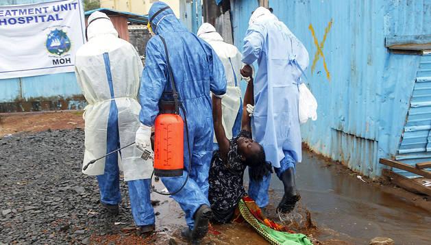 Enfermeros liberianos cargan con una paciente sospechosa de tener ébola