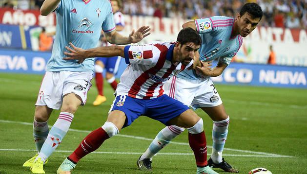 Raúl García protege el balón ante Fontás y Cabral