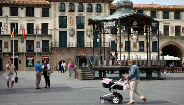 Varias personas pasean junto al quiosco de la plaza de los Fueros, centro neurálgico de Tudela.