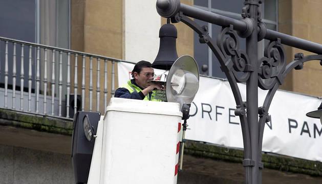 Un operario cambia la bombilla de una farola en la plaza del Castillo