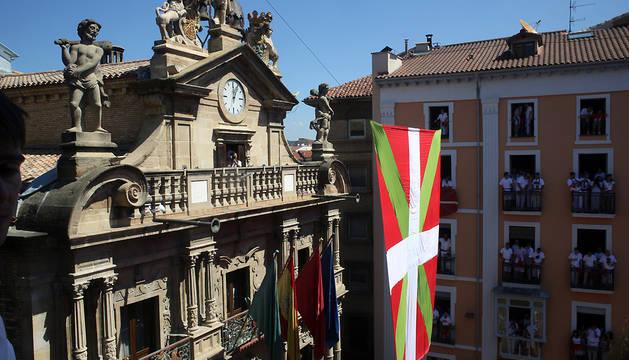 Momento en el que la ikurriña gigante tapa la fachada del Ayuntamiento pamplonés