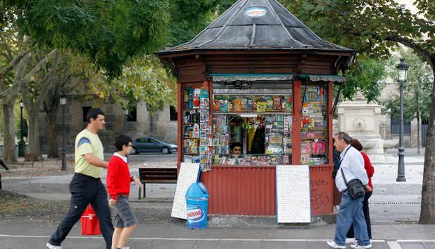 Varias personas pasan por delante del kiosko de chucherías de la plaza de Recoletas.