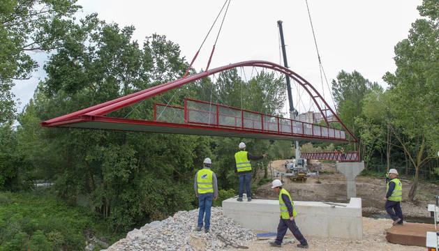 Varios operarios supervisan la colocación de la nueva pasarela del Parque Fluvial del Arga en Landaben.