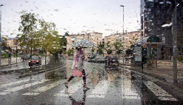 Una vecina de Pamplona cruza un paso de cebra bajo la lluvia