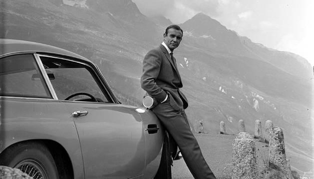 Foto cedida por el museo Kunsthal del actor Sean Connery descansando en el parachoques de su Aston Martin DB5 durante el rodaje de 'James Bond contra Goldfinger' en los Alpes Suizos
